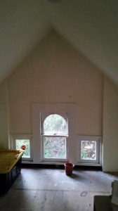 Before shot of the attic!  Notice the plywood floor, no lighting and the off white walls and ceiling.